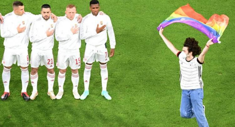 Supporter loopt met regenboogvlag het veld op bij aanvang EK-wedstrijd tegen Hongarije